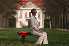 Success woman. Businesswoman sitting at the front of her mansion stock photos