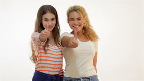 Success woman showing thumbs up. Excited beautiful woman isolated on white background. Two young girlfriends standing together. Brown-haired caucasian and red stock video footage