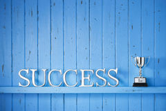 Success Trophy Winner Background. A blue painted wood background with the word success on it