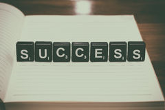 Success word from black plastic blocks on notebook with vintage filter Royalty Free Stock Photo