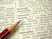 'success' word in dictionary. 'success' word in english-spanish dictionary with pencil Stock Photos