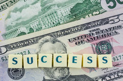 Success word on dollar background. Finance concept Stock Photos