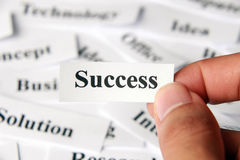 Success. Word paper in hand with the background of other words royalty free stock photography