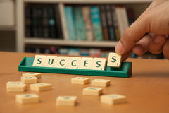 SUCCESS word in scrabble letters. Player's hand forming the word SUCCESS with Scrabble letters Royalty Free Stock Images