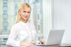 Success at work. The friendly and confident young woman sitting Royalty Free Stock Images