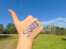 Success written on hand with thumb up. With green grass and a blue sky background royalty free stock photos
