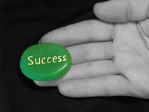 Success at your fingertips. Photo of a green stone engraved with the word success, being held on the fingertips of a black and white hand Stock Photos