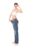 Successes girl after diet. Successes  girl in large trousers after diet, expressing emotion, on white background Stock Photography