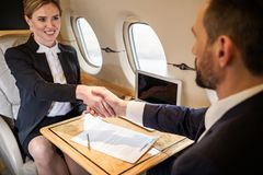 Successful adult people concluding contract. Contented young businesswoman shaking hands with her companion in airplane, contract is lying on tray table between stock images