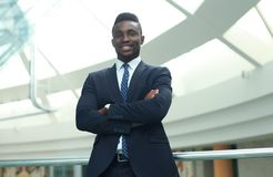 Successful African American businessman businessman standing in office. stock photo