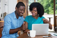 Successful african american love couple with laptop Stock Photo