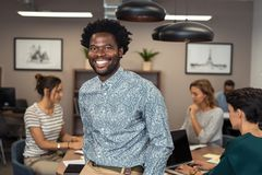 Successful african business man smiling. Portrait of happy african businessman looking at camera and sitting at desk. Mature business men in office with stock images