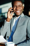 Successful African Businessman Smiling with Phone Stock Images
