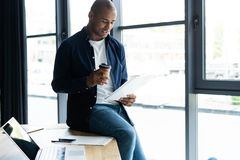 Successful African entrepreneur studying documents with attentive and concentrated look, drinking coffee at cafe. Dark. Successful African entrepreneur studying stock photo