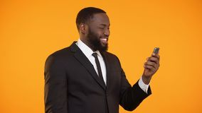 Successful afro-american businessman reading news on phone, making yes gesture. Stock footage stock video