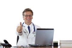 Successful aged doctor at desk holding thumb up Stock Image