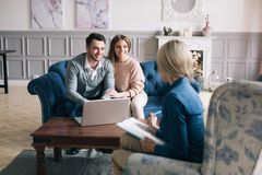 Successful agent giving consultation to family couple about buying house. Consultation royalty free stock photo
