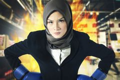 Successful and aggressive young muslimah businesswomen with boxing glove over abstract double exposure background. Creative ideas concept, successful and Stock Photography