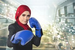 Successful and aggressive young muslimah businesswomen with boxing glove over abstract double exposure background. Creative ideas concept, successful and Royalty Free Stock Image