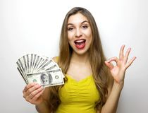 Successful american woman holding fan of money dollar bills and showing ok sign isolated over white background.  stock photography