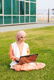 Successful Arab woman and laptop. Arab businesswoman wearing hijab working on a laptop in the park. Stock Images