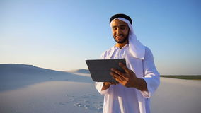 Successful Arabian businessman holds in hands and uses tablet, standing among big desert on summer evening. Handsome Muslim businessman with tablet solves stock footage