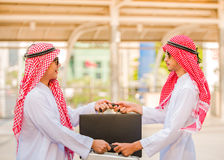 Successful Arabic business people shaking hands exchange bag over a deal. Royalty Free Stock Photo