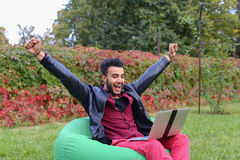 Successful Arabic Young Businessman Sits With Laptop in Chair, S. Perspective Young Arabic Guy, Businessman, Student Sits With Laptop in Soft Green Chair, Looks Royalty Free Stock Photo
