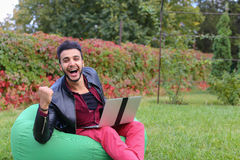 Successful Arabic Young Businessman Sits With Laptop in Chair, S. Perspective Young Arabic Guy, Businessman, Student Sits With Laptop in Soft Green Chair, Looks Royalty Free Stock Photos