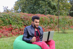 Successful Arabic Young Businessman Sits With Laptop in Chair, S. Perspective Young Arabic Guy, Businessman, Student Sits With Laptop in Soft Green Chair, Looks Stock Images