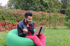 Successful Arabic Young Businessman Sits With Laptop in Chair, S. Perspective Young Arabic Guy, Businessman, Student Sits With Laptop in Soft Green Chair, Looks Royalty Free Stock Photography