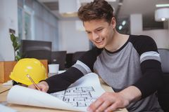 Successful architect working on blueprints at the office royalty free stock photo