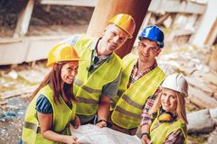 Successful Architects Team. Four construction architects in the building damaged in the disaster. Smiling and looking at camera Stock Photo