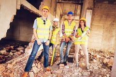 Successful Architects Team. Four construction architects in the building damaged in the disaster. Smiling looking at camera Royalty Free Stock Photography