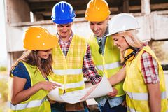 Successful Architects Team. Four construction architects in the building damaged in the disaster. They are smiling and looking at plan Royalty Free Stock Image