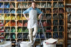 Successful Artisan. Full length portrait of modern artisan wearing apron standing on step ladder and posing in workshop against shelves with materials, copy stock photography