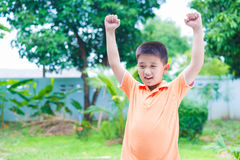 Successful Asian boy punching the air with his fists in air, smi Stock Images