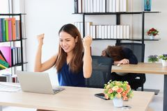 Successful Asian business woman raising hands with competitor colleague bend down head on the desk in office. Successful Asian business women raising hands with stock images