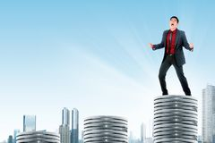 Successful asian businessman standing on the highest silver coins. Over skyscrapers background royalty free stock photography