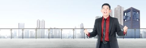 Successful asian businessman standing on modern terrace. With cityscapes background stock photography