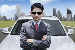 Successful Asian businessman wearing sunglasses in front of luxury car. With cityscape background Stock Photos