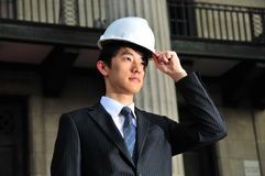 Successful Asian Engineer putting on his hard hat Stock Photography