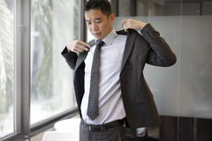 Successful asian man putting on his suit ready for meeting Stock Photo
