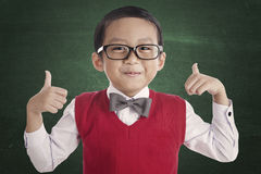 Successful asian student. Portrait of asian elementary school student and thumbs-up. shot in the classroom Stock Images