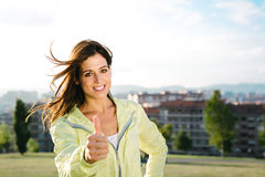 Successful athlete doing thumbs up gesture. Sporty urban woman doing success thumbs up gesture after exercising outdoor. Healthy and sport lifestyle concept Stock Photo