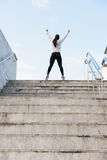 Successful athlete raising arms after running on urban stairs royalty free stock images