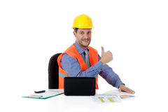 Successful attractive caucasian man architect. With safety helmet in the office with laptop. Thumb-up. Studio shot. White background stock image