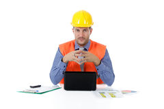 Successful attractive caucasian man architect. With safety helmet in the office sitting at desk with laptop. Studio shot. White background stock image