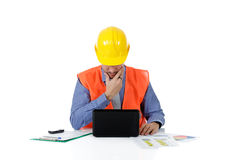 Successful attractive caucasian man architect. With safety helmet in the office with laptop and the hand on beard. Studio shot. White background royalty free stock image