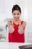 Successful attractive indian businesswoman with thumbs up at off Stock Photos